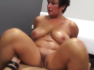 Busty MILF oils up and fucks